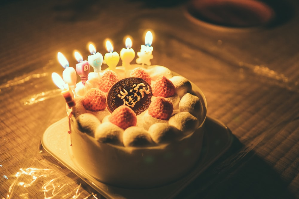 white and brown cake with lighted candles