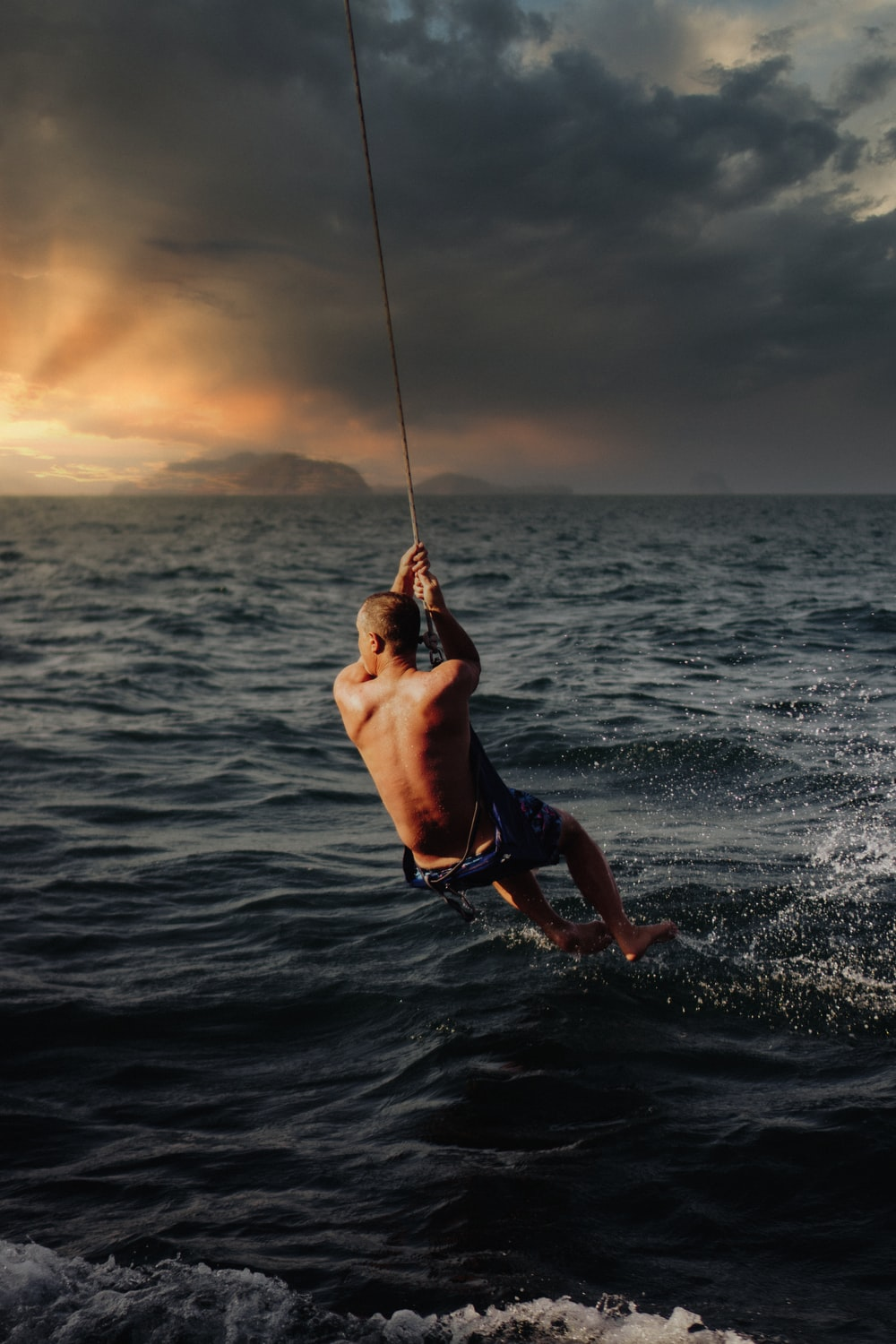 man in black shorts holding rope on body of water during daytime