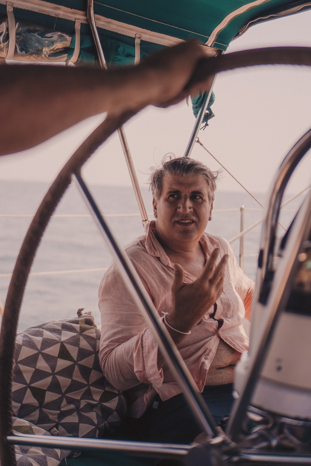 man in brown and white stripe polo shirt sitting on boat during daytime