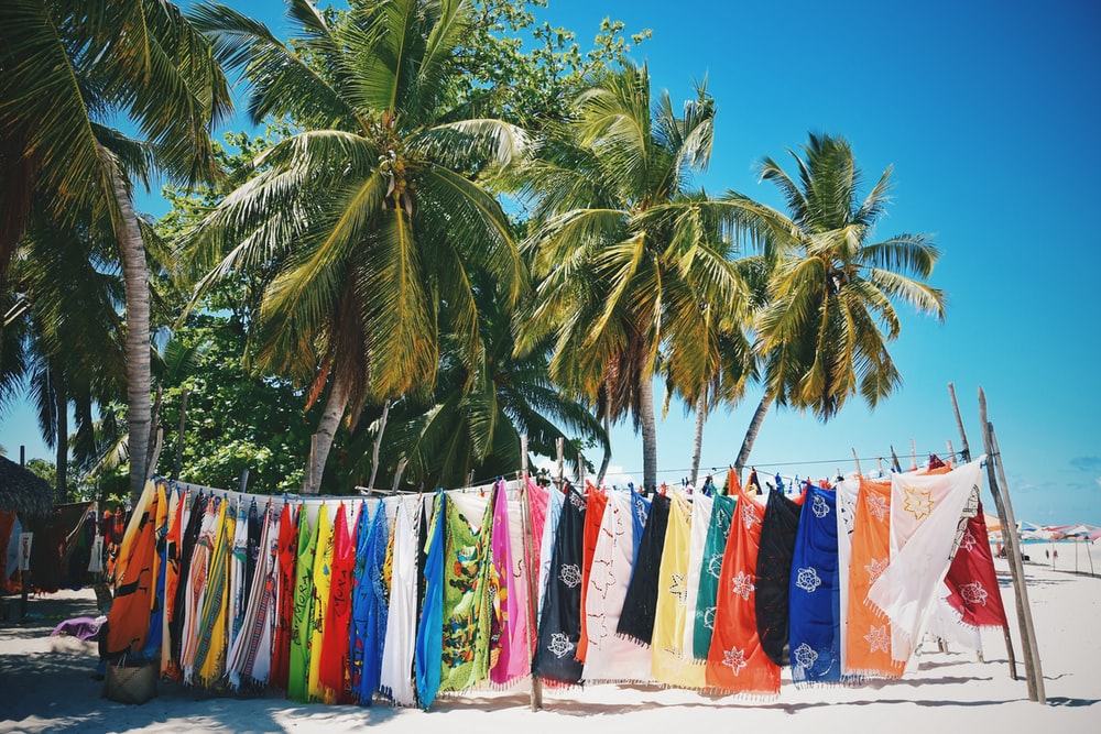 assorted color textiles on green coconut palm tree under blue sky during daytime