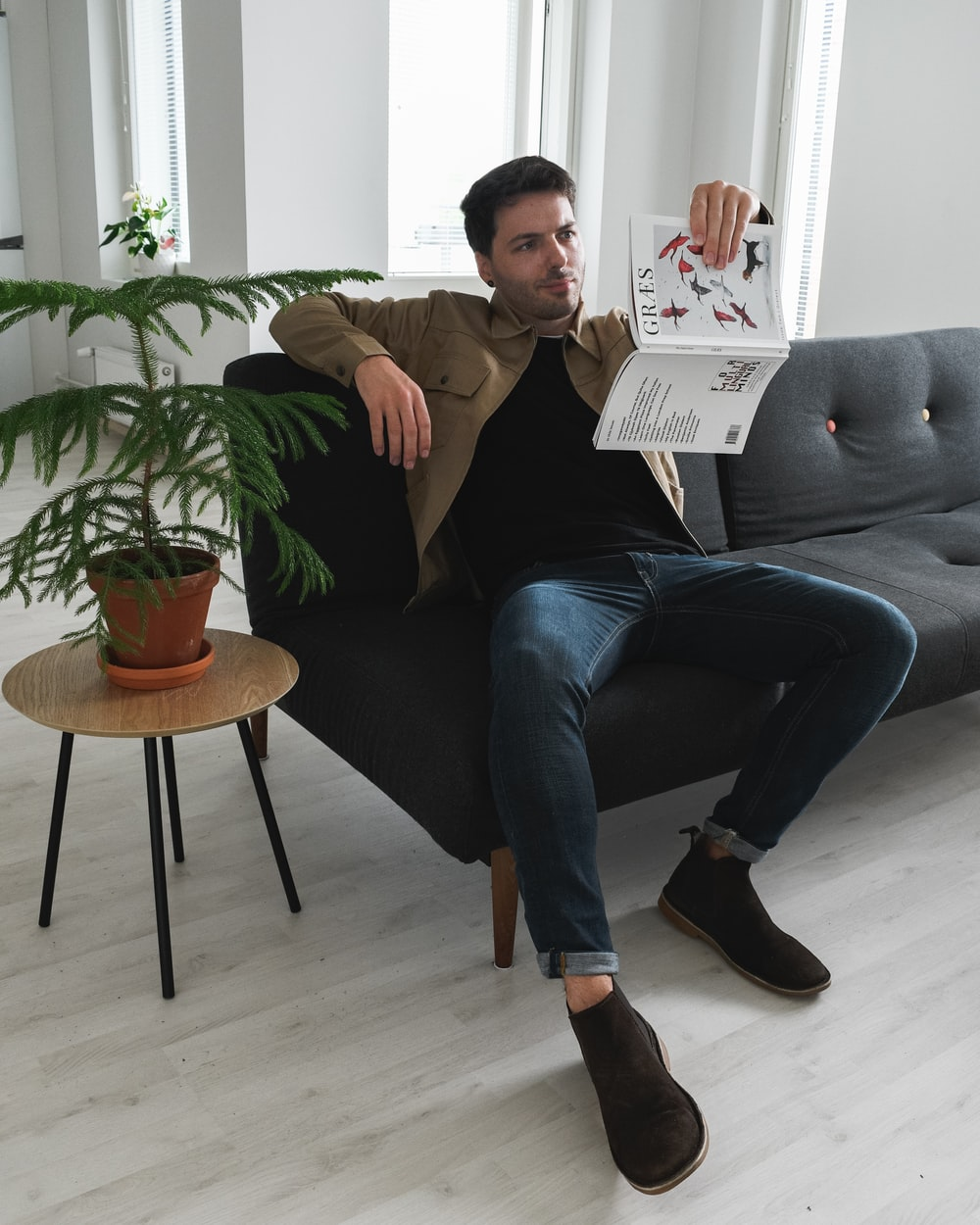 man in black polo shirt and blue denim jeans sitting on gray sofa