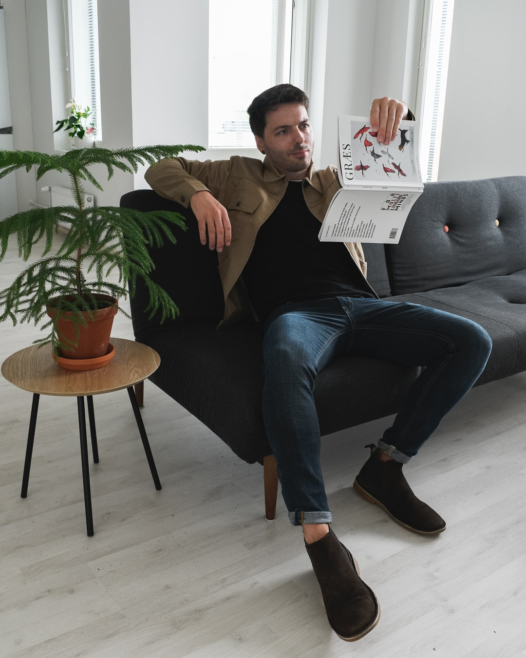 Jon reading a vertically-printed article in GRÆS Magazine