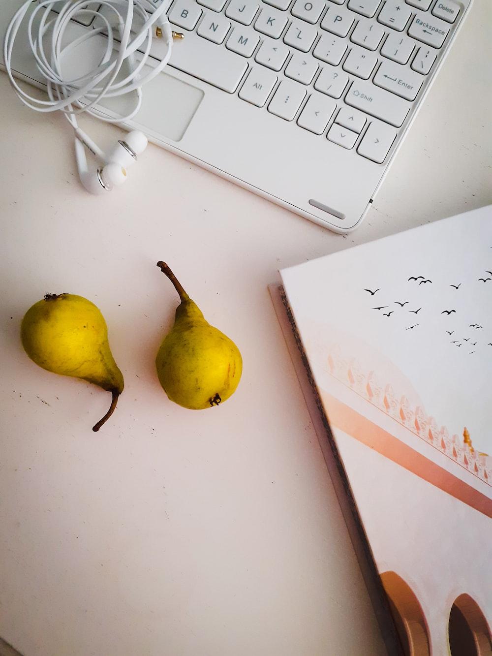 yellow round fruit beside white apple earpods