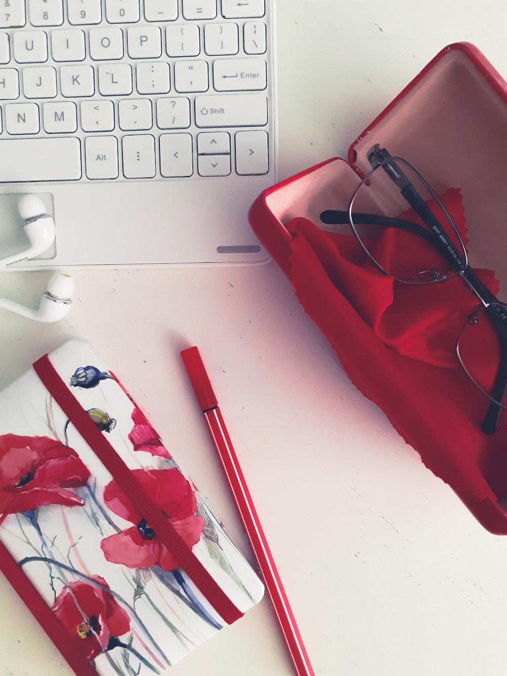 red framed eyeglasses on white laptop computer