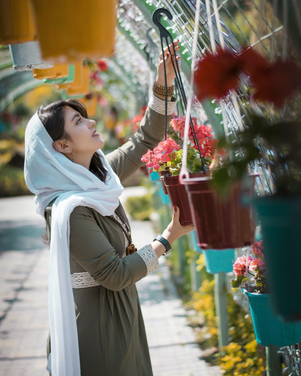 woman in white hijab holding red flower bouquet