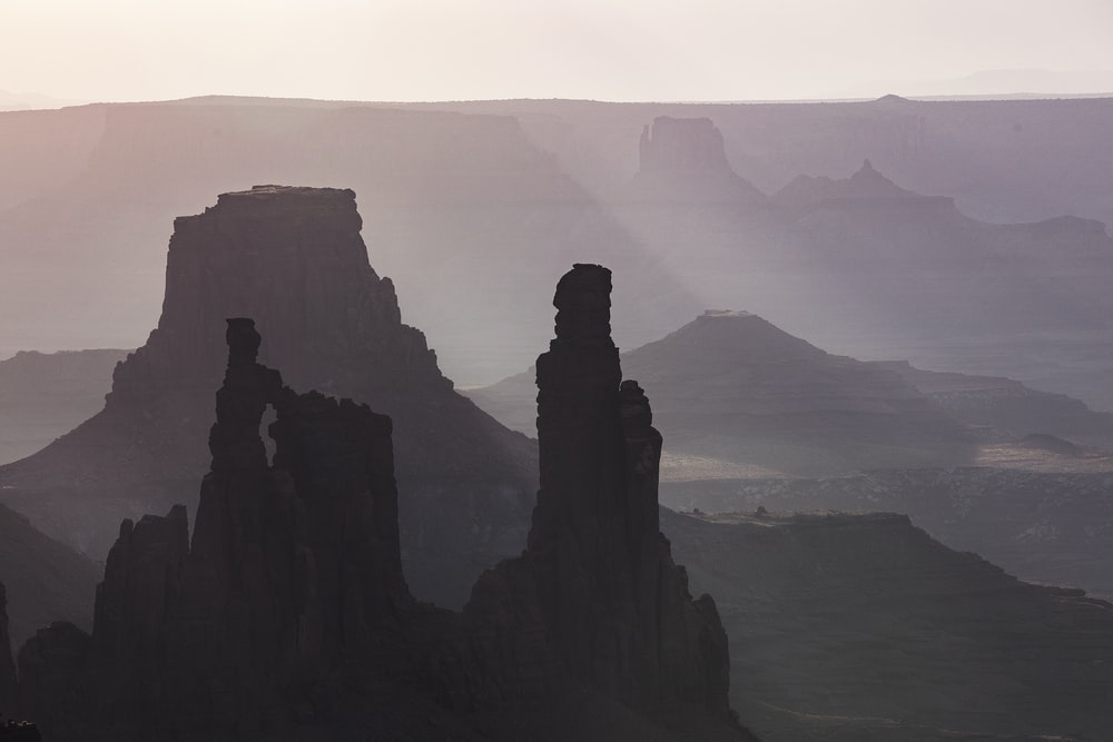 silhouette of rock formation near body of water during daytime