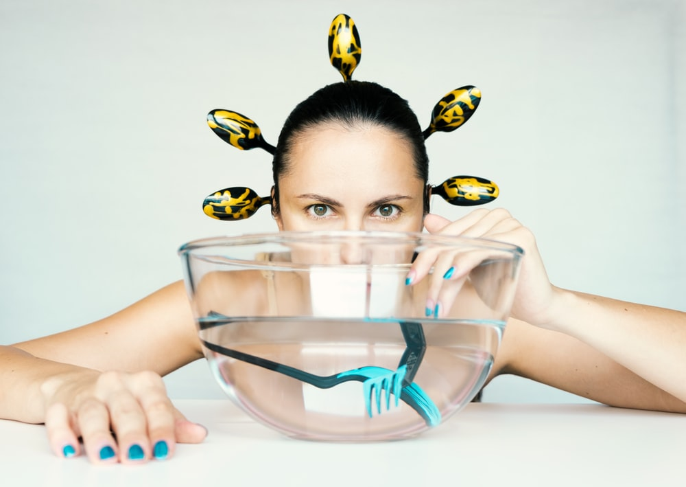 woman holding clear glass bowl with blue and yellow beads