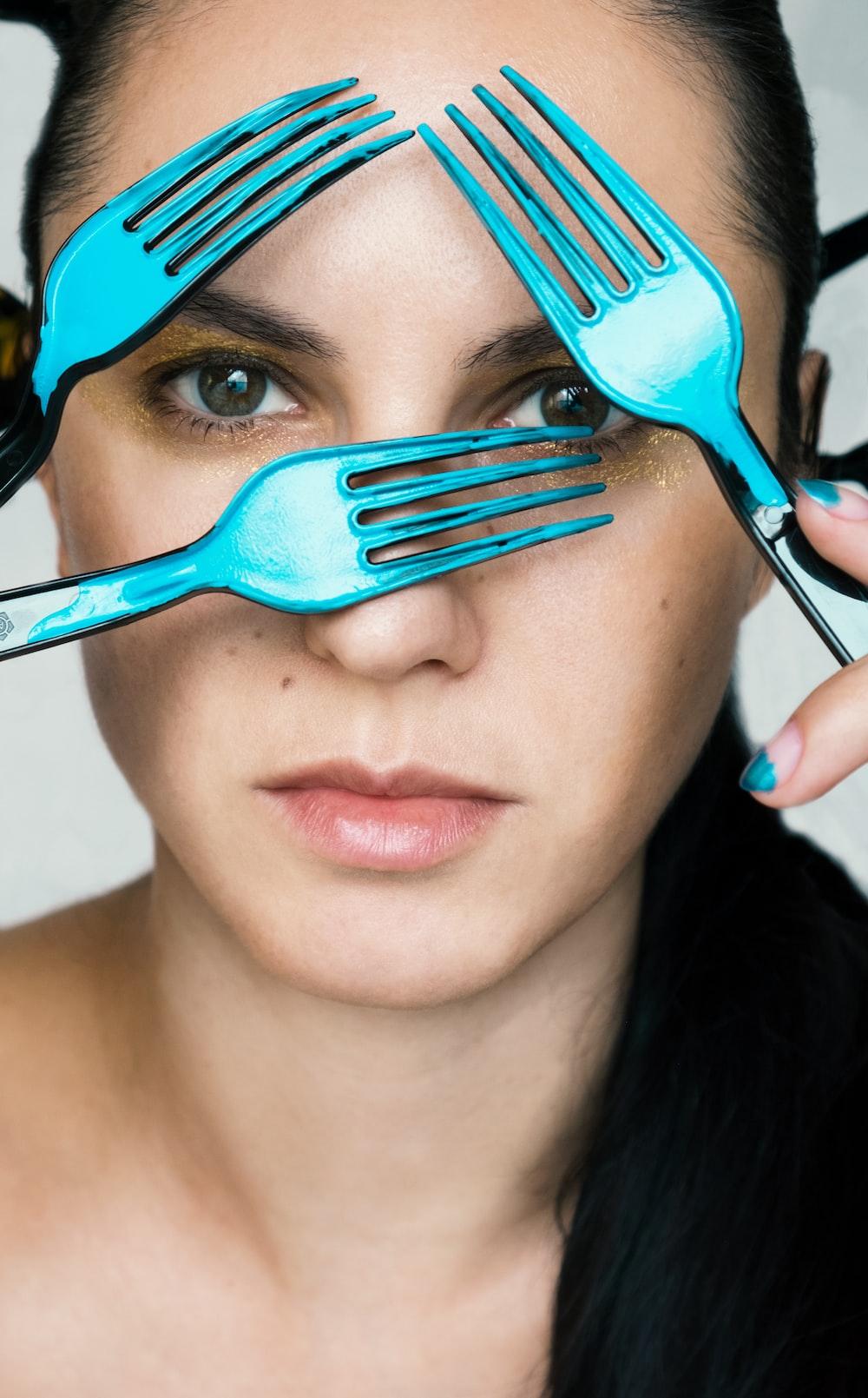 woman holding blue plastic fork