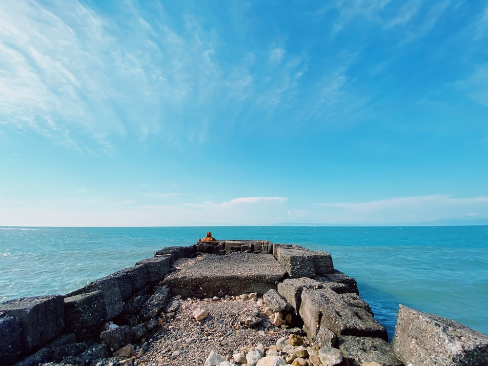 person sitting on rock formation near sea under blue sky during daytime