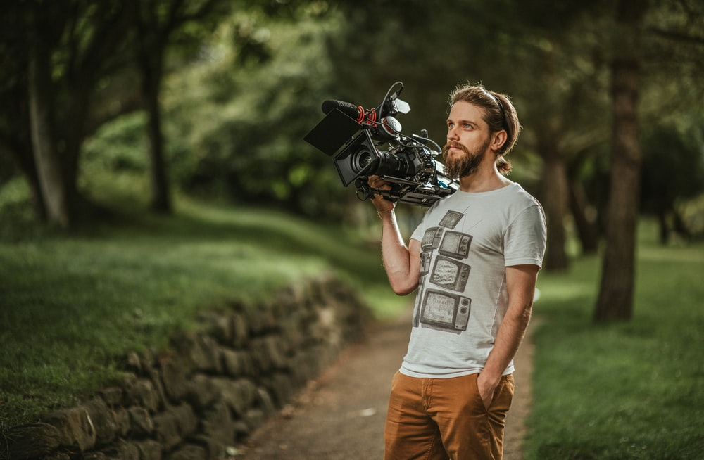 man in gray crew neck t-shirt and brown pants holding black dslr camera