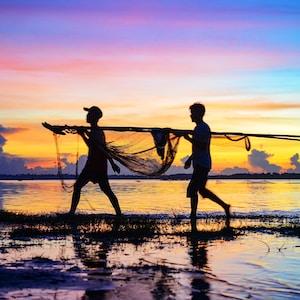 silhouette of 2 men holding fishing net on beach during sunset