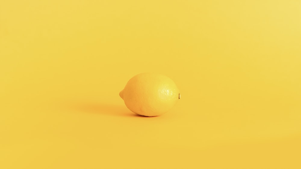 yellow lemon fruit on yellow surface