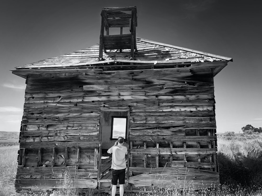 woman in white shirt and black pants standing on wooden house