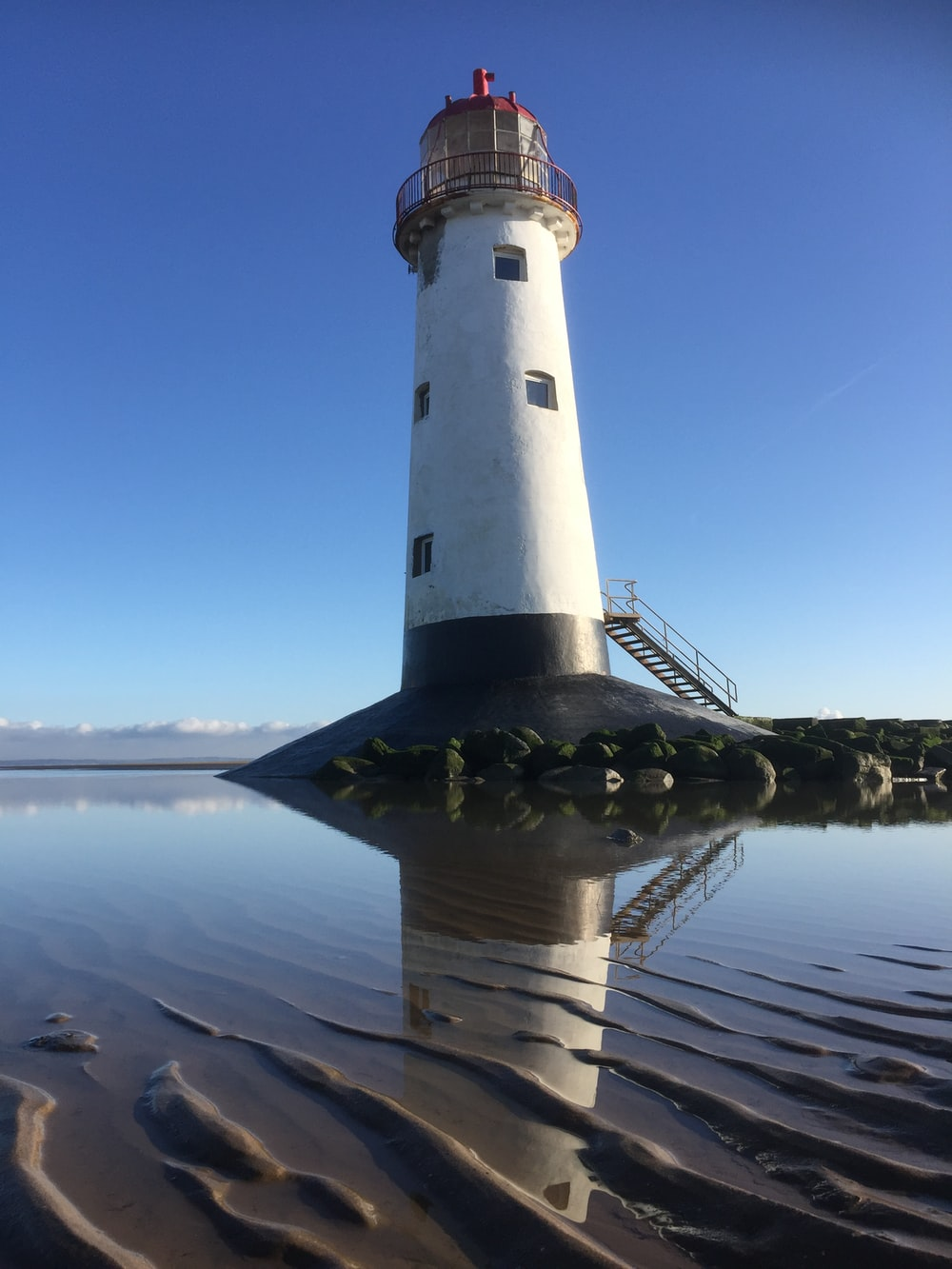 white and black lighthouse near body of water during daytime
