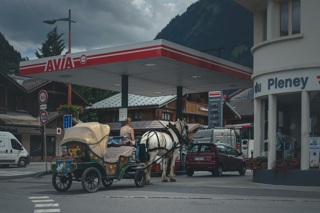 A real carriage with a horse stands at the gas station.