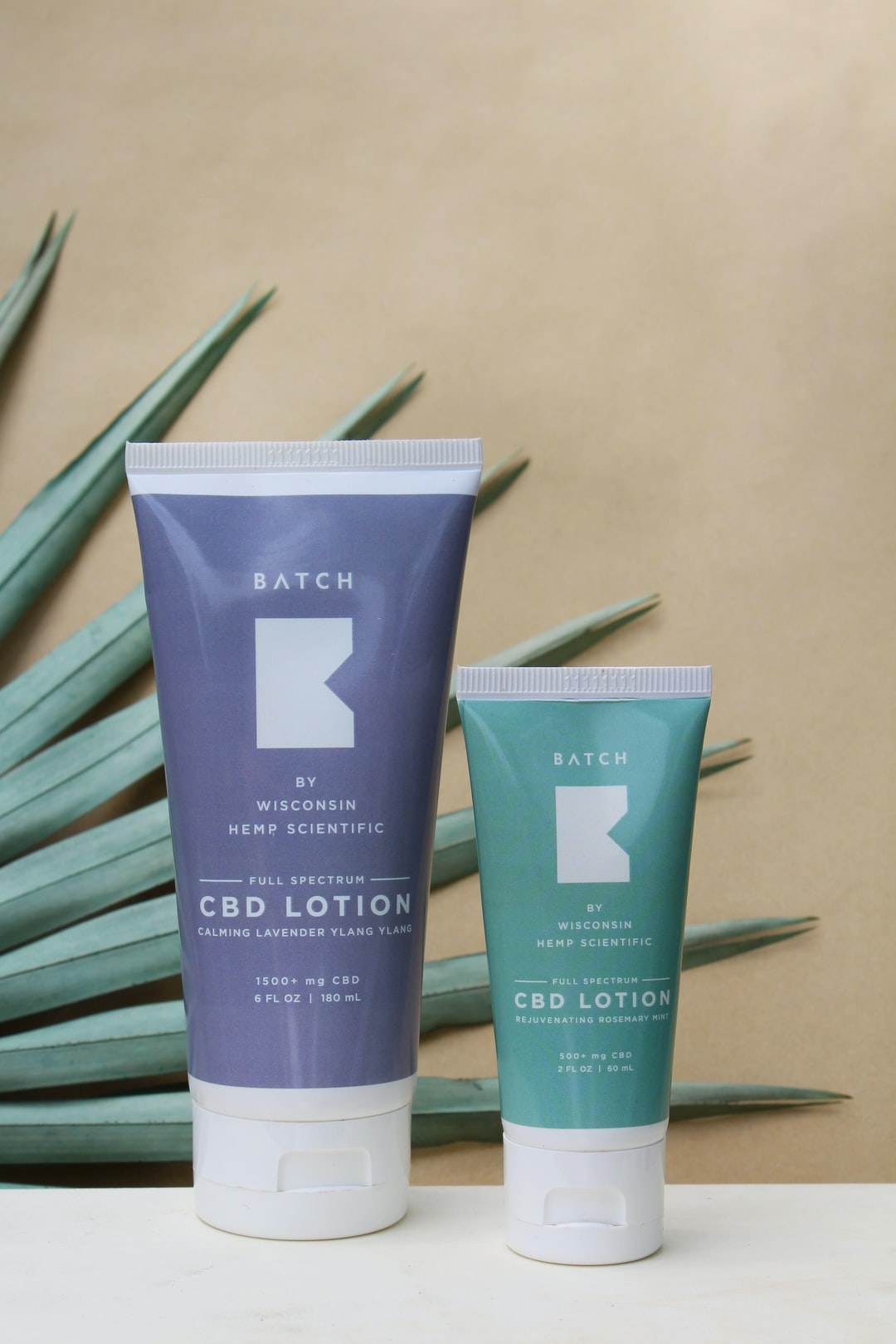CBD lotion bottles on counter top with palm leaves and solid yellow background