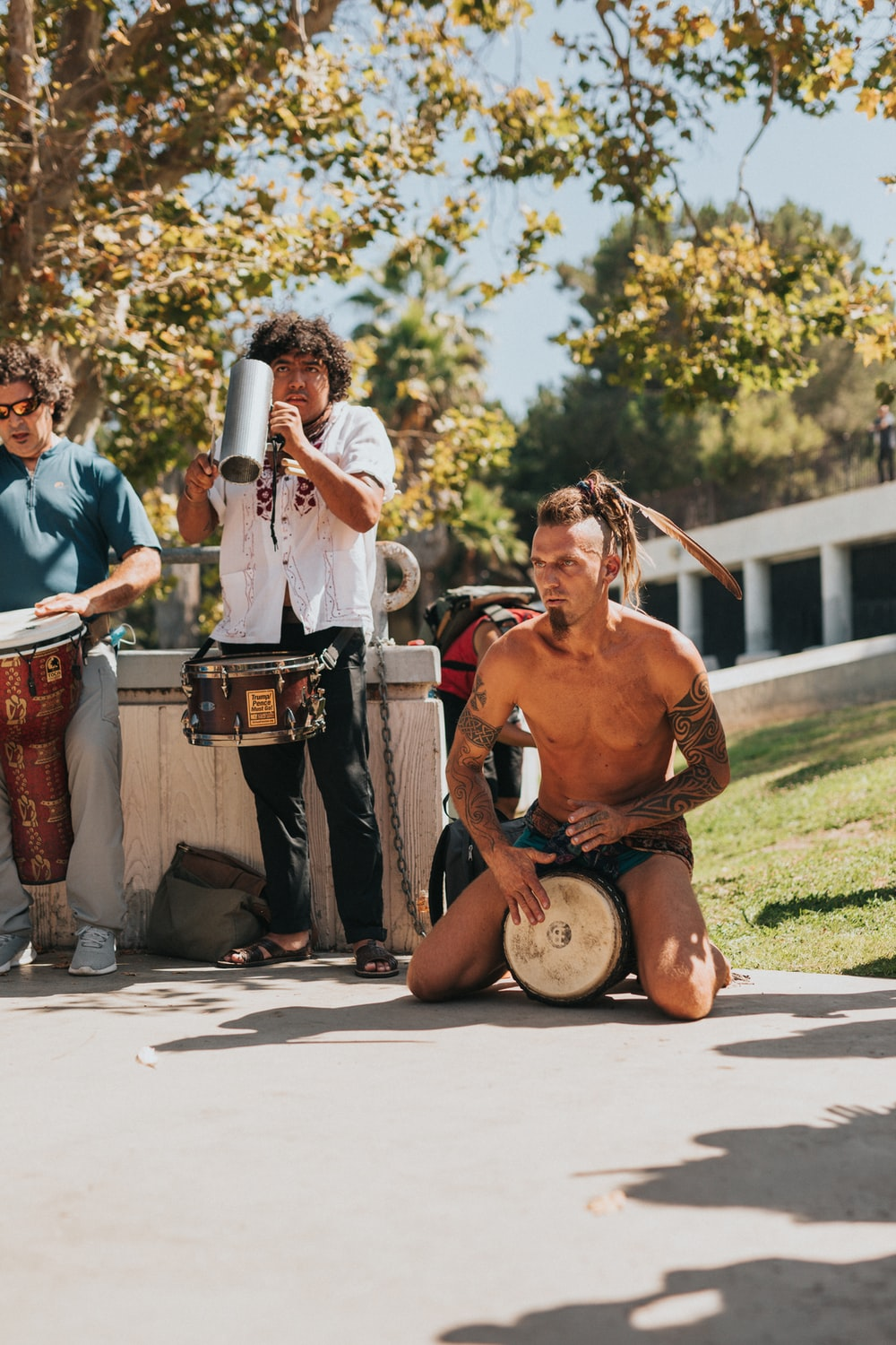 topless man in black shorts playing drum during daytime