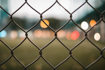 grey metal fence with yellow light