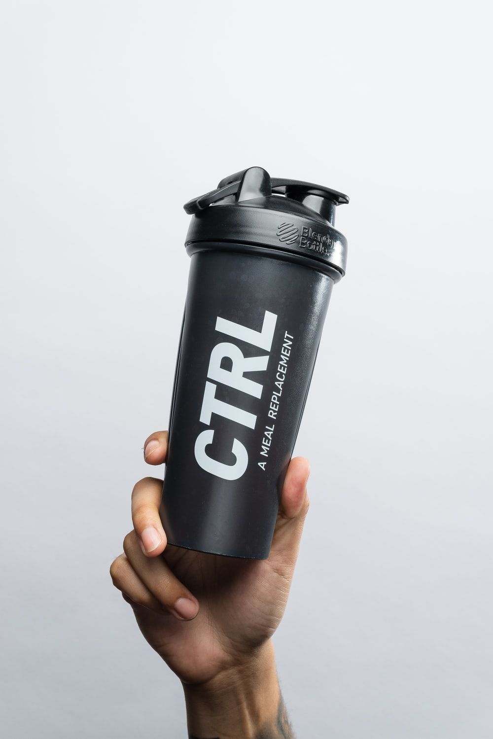 person holding black and white adidas tumbler