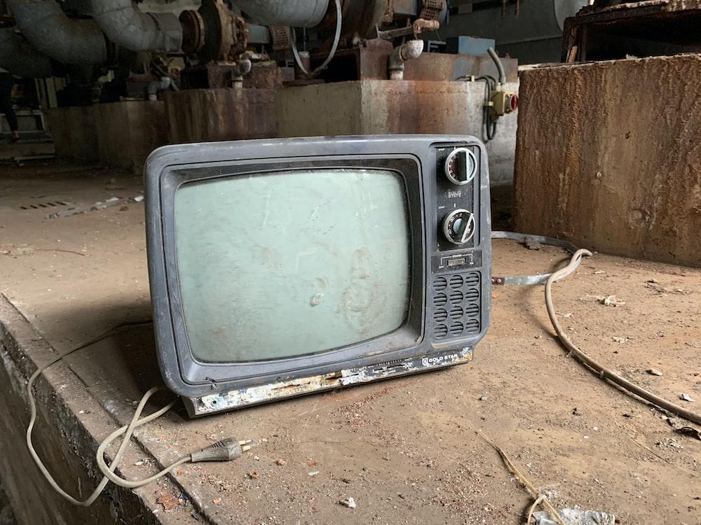 gray crt tv on brown soil