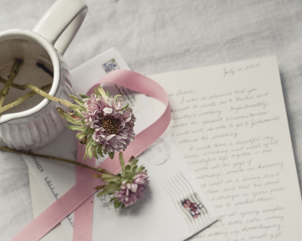 pink and white floral ribbon on white printer paper