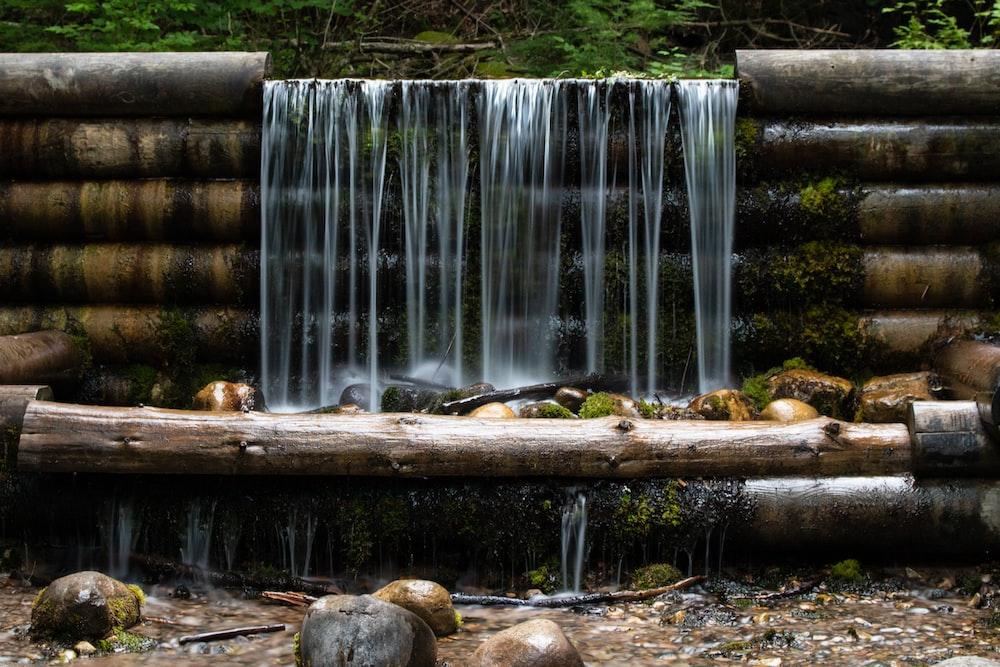 brown rocks on brown wooden log near waterfalls