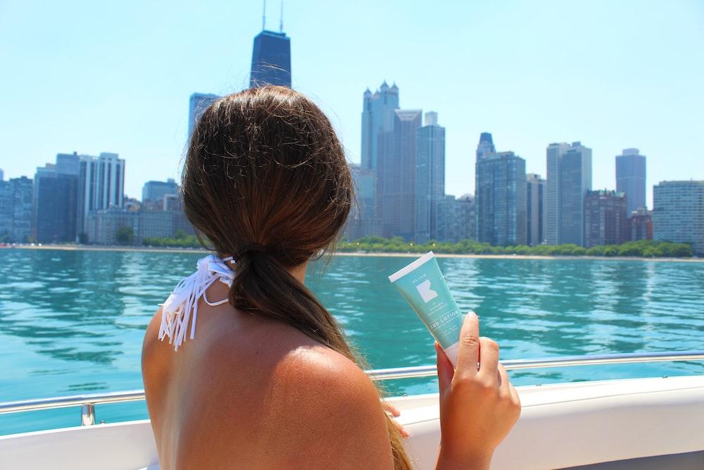 woman in pink bikini reading book on boat during daytime