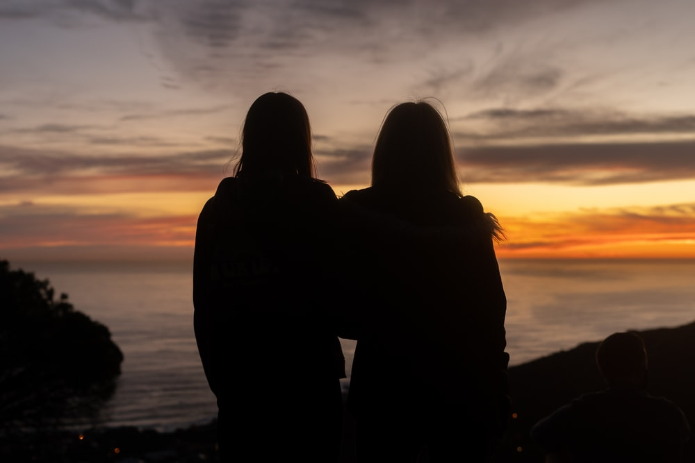 silhouette of man and woman standing on seashore during sunset