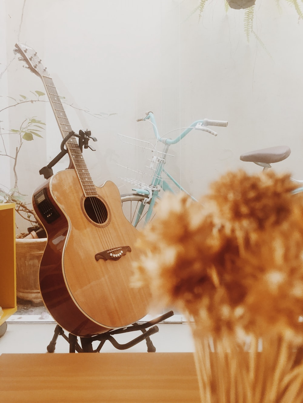 brown acoustic guitar on white wall