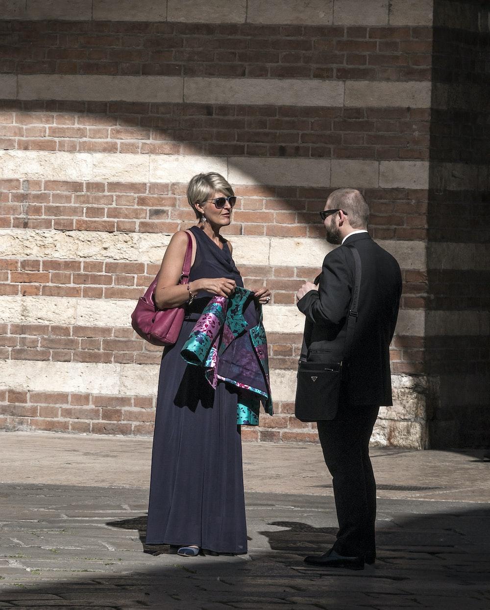 man in black suit standing beside woman in black dress