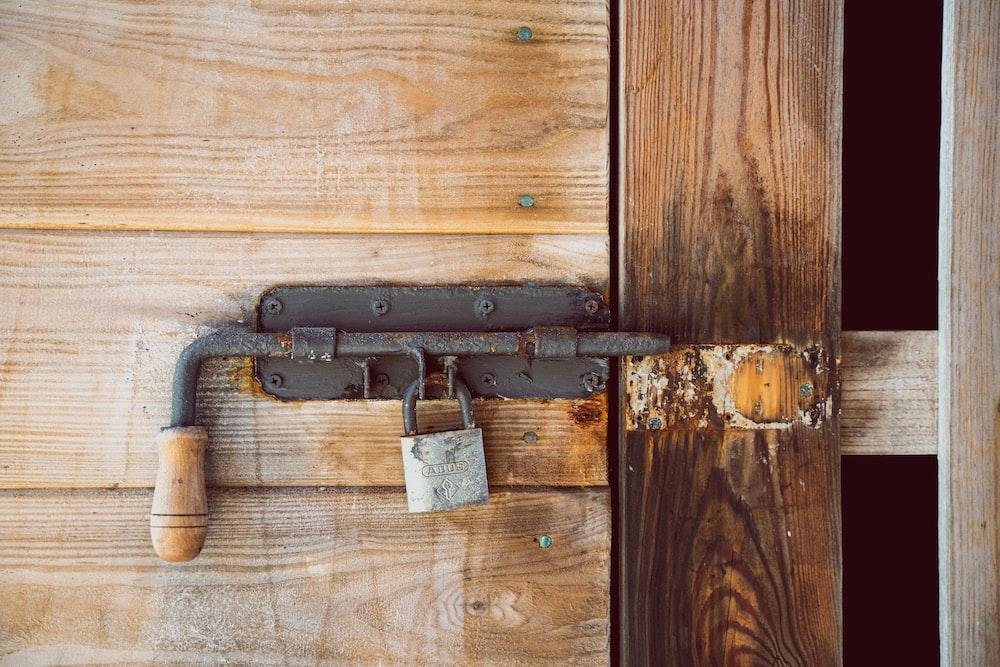 black and silver padlock on brown wooden door