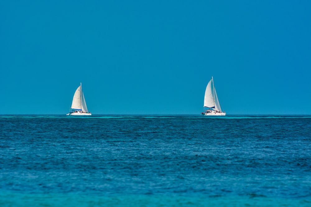 white sailboat on sea under blue sky during daytime