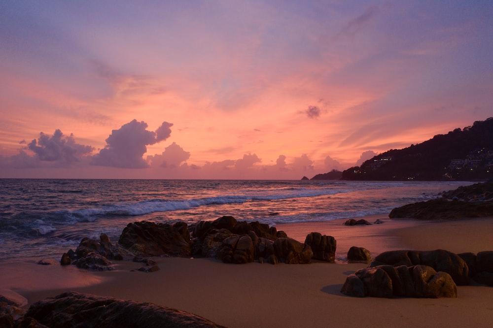 brown rocks on seashore during sunset