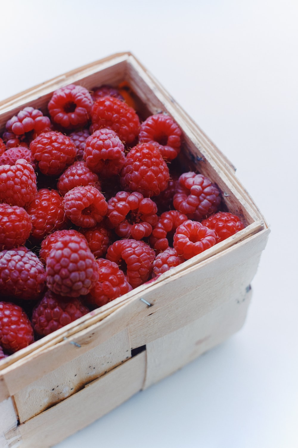 red strawberries in brown wooden crate