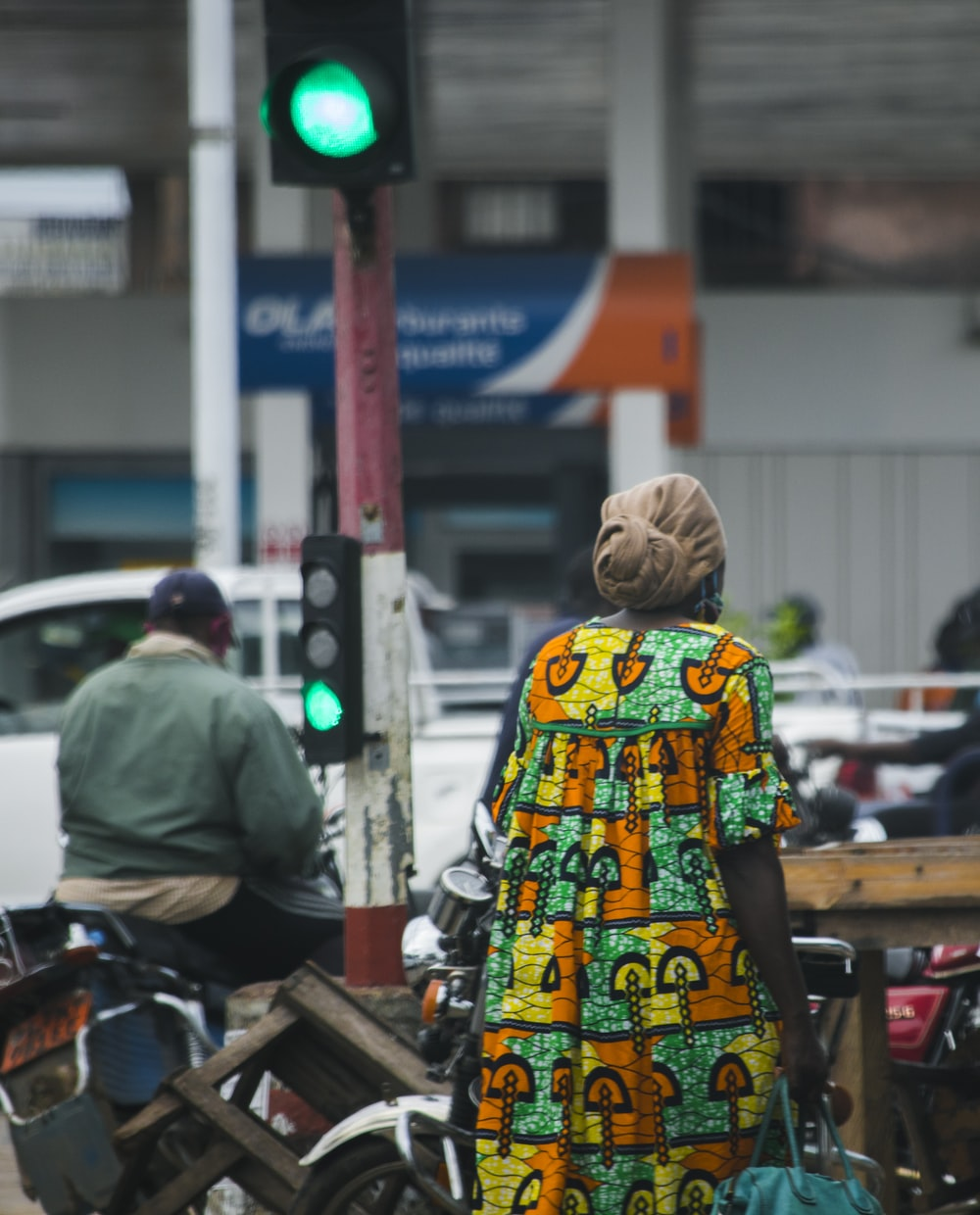 woman in yellow green and white floral dress standing on sidewalk during daytime