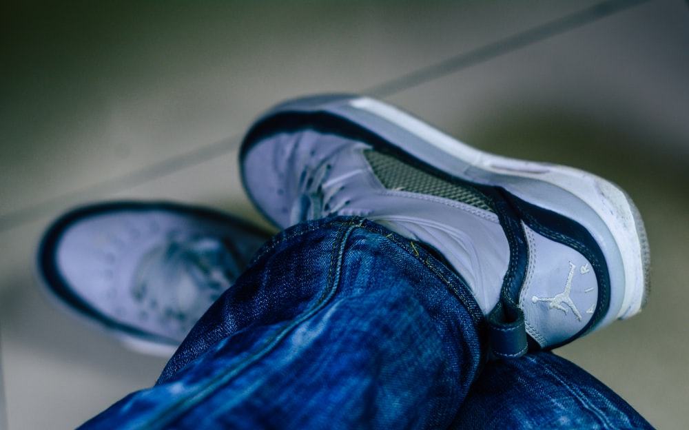 person in blue denim jeans and black and white nike athletic shoe