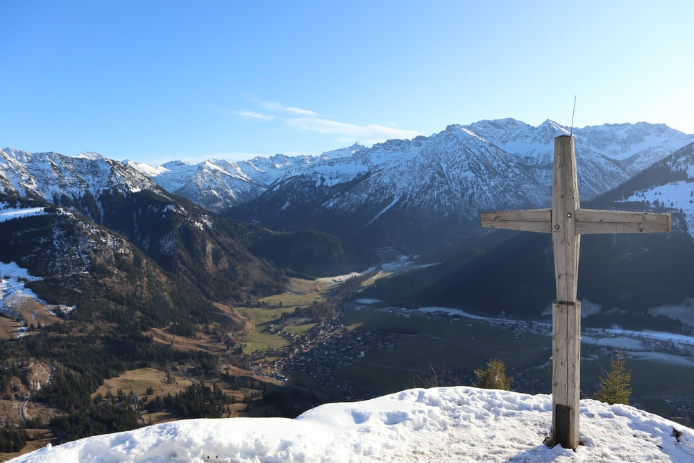 brown wooden post on snow covered ground near mountains during daytime