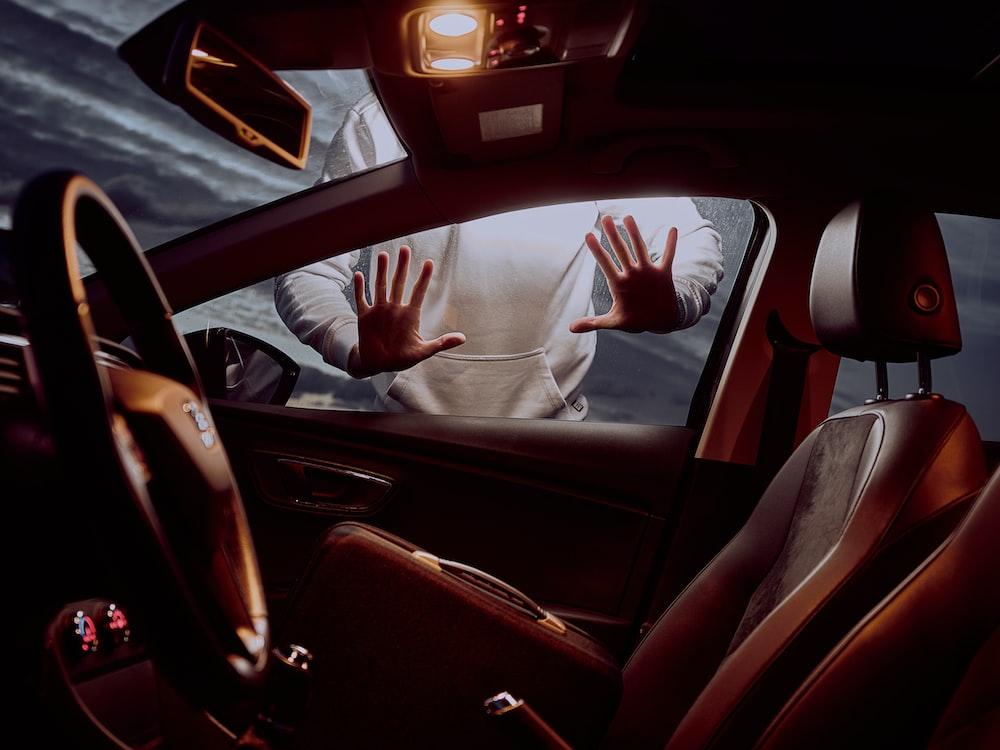 man in white long sleeve shirt driving car