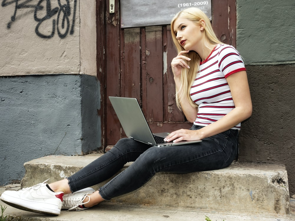 woman in white and red striped shirt and blue denim jeans sitting on concrete bench using