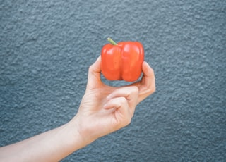 person holding red bell pepper