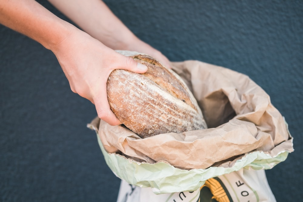 person holding bread with brown powder