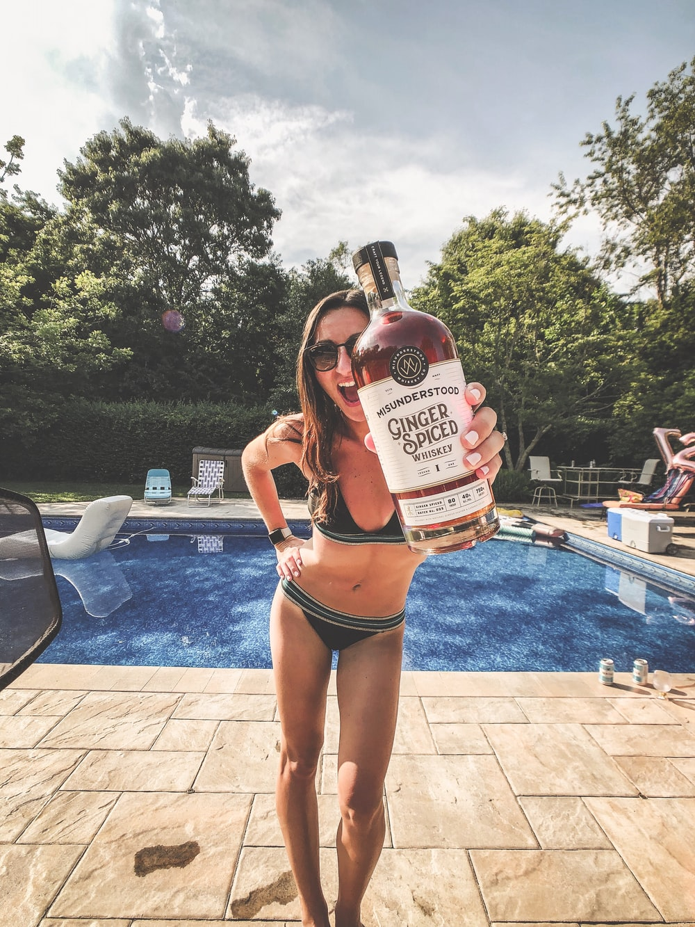 woman in black bikini holding white and red labeled bottle