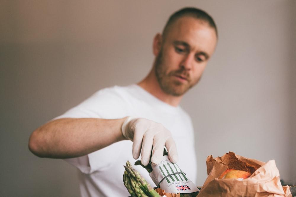 man in white crew neck t-shirt holding green vegetable