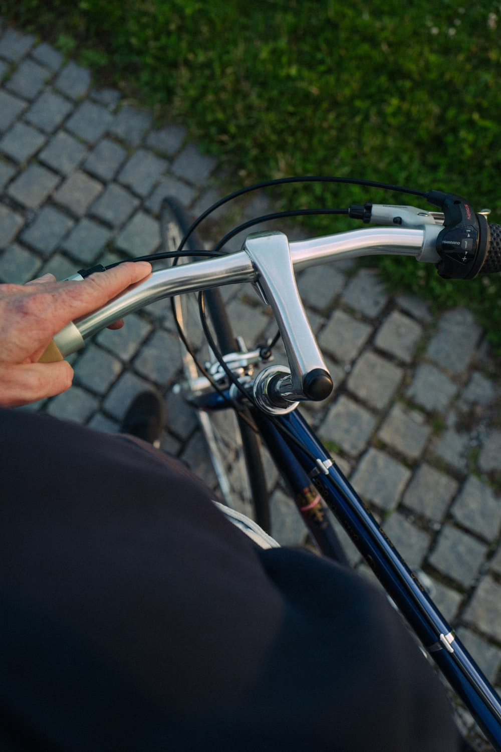 person holding gray bicycle handle bar