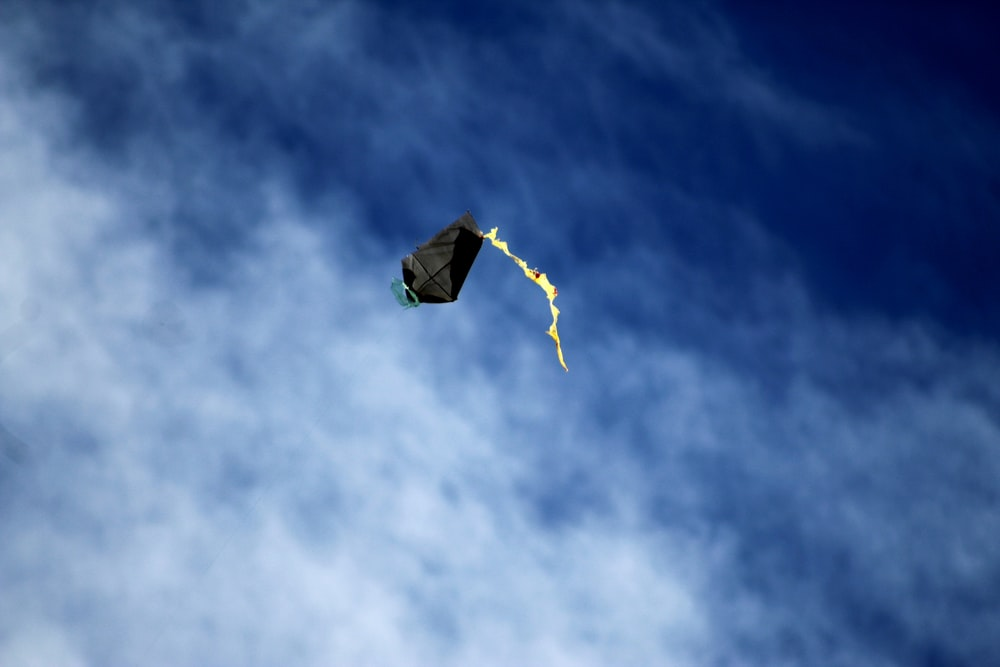 yellow and orange kite flying in the sky during daytime