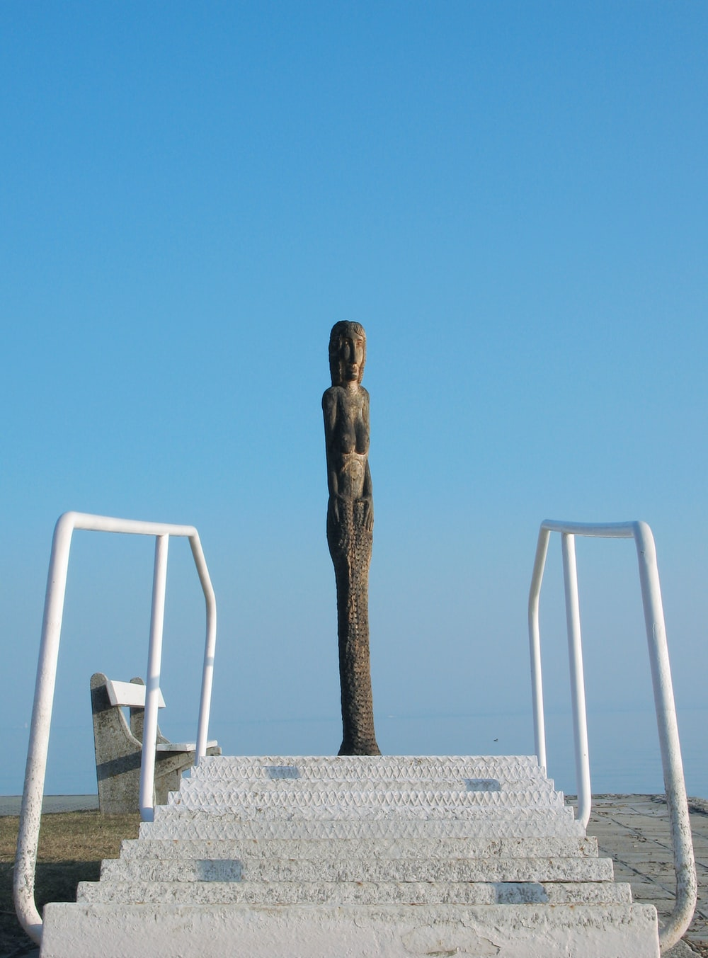 white wooden chair near statue under blue sky during daytime