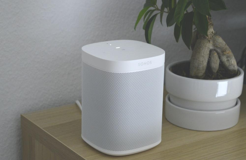 white portable speaker on brown wooden table