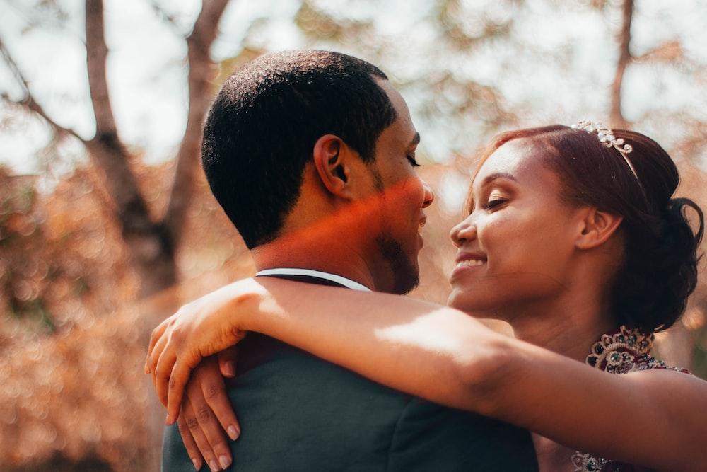 man in black shirt kissing woman in white shirt