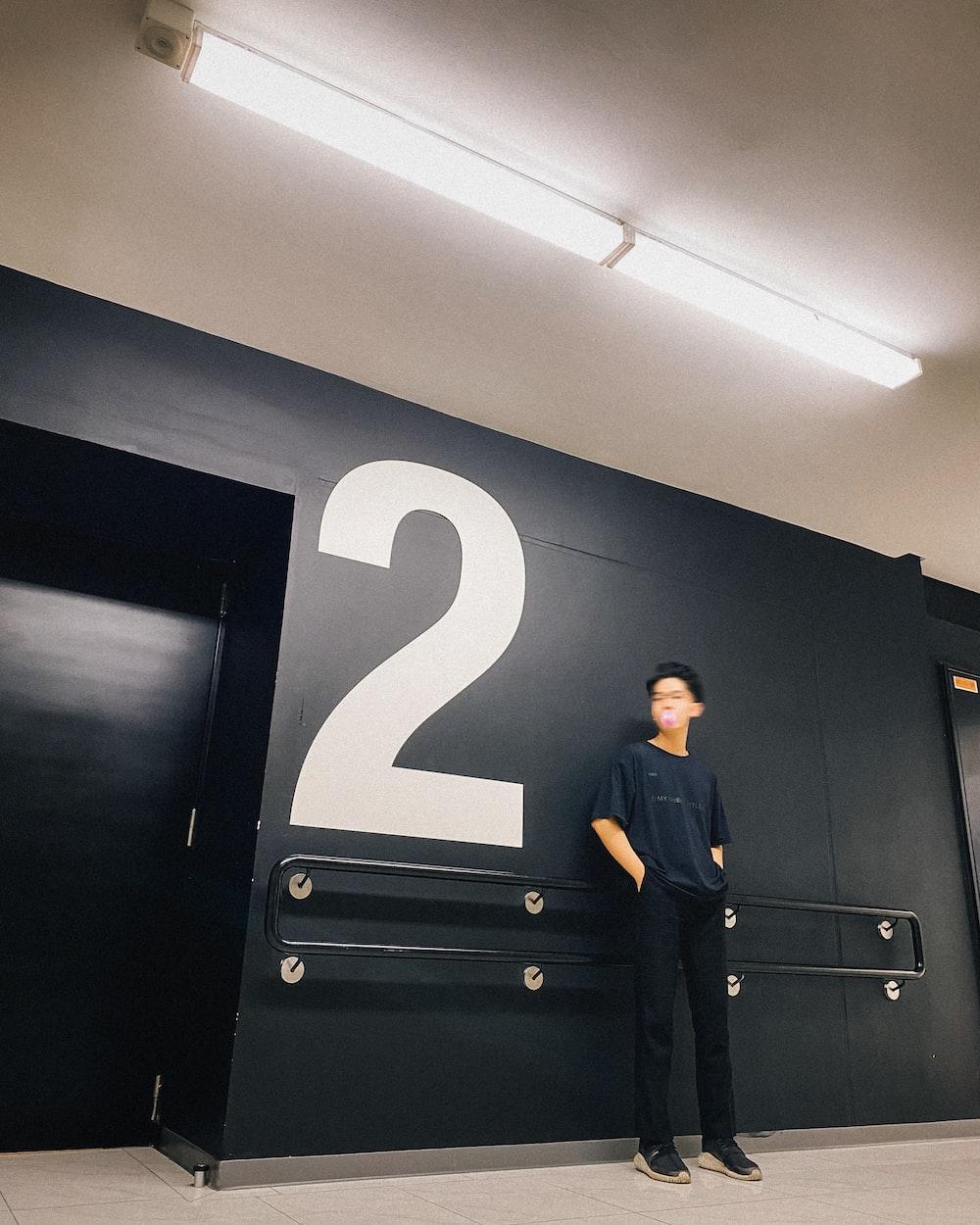 man in black suit standing beside black wooden door