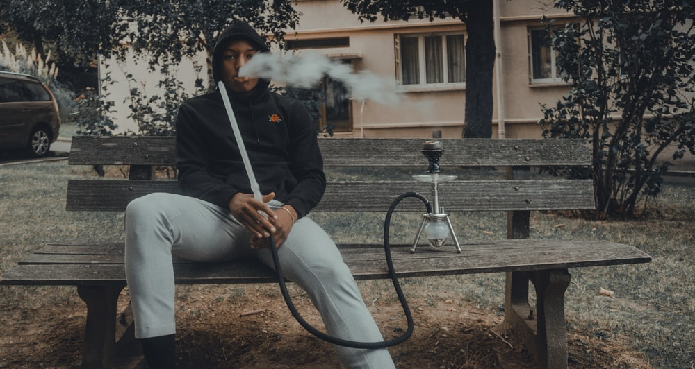 man in black zip up jacket smoking cigarette